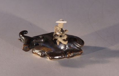 Image: Ceramic Figurine  - Man Sitting on Water Buffalo 2.75x1.25x1.5
