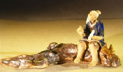 Miniature Ceramic Figurine Man Sitting On A Log - Blue Color