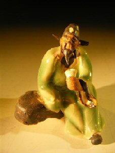 Image: Ceramic Miniature Figurine Man on Bench Holding Drinking Cup