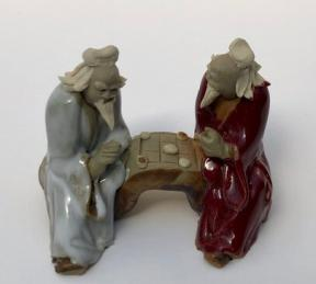 Ceramic Figurine<br>Two Men Sitting On A Bench<br>Color: White & Red