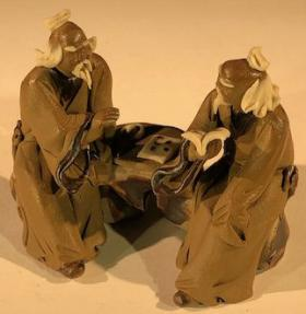 Ceramic Figurine<br>Two Mud Men Sitting On A Bench Reading Books - 2.5